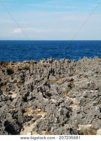 Sea horizon rocks and sky. Bali ocean view background. Beautiful landmark Stone Island Coastline with blue ocean