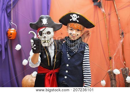 Two Little Boys In Different Pirate Costumes With Faceart Are Having Fun At The Halloween Party