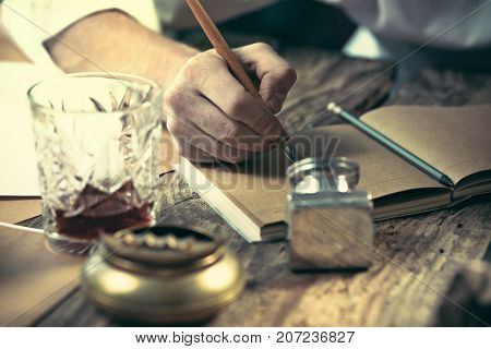 Writer at work. The hands of young writer sitting at the table and writing something in his sketchpad at home