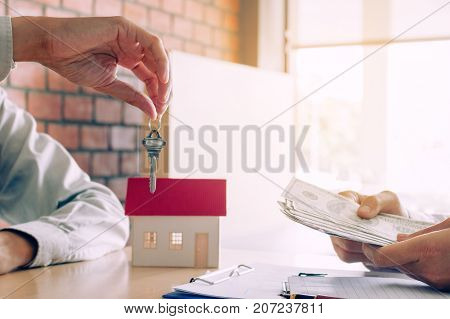 Salesman home brokers provide key to new homeowners and buyers giving money for salesman.