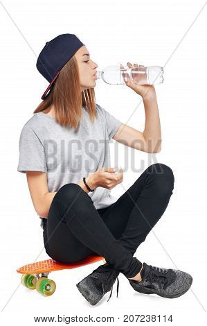 Teen girl in full length sitting on skate board drinking water from a bottle isolated on white background