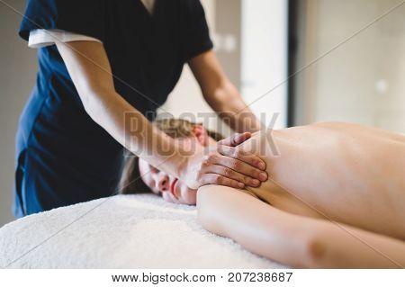 Masseur treating masseuse at spa wellness saloon