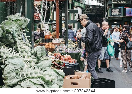 LONDON, UK - SEPTEMBER 30, 2017: Man looking at the vegetables on a market stall in Borough Market, one of the largest and oldest food markets in London.