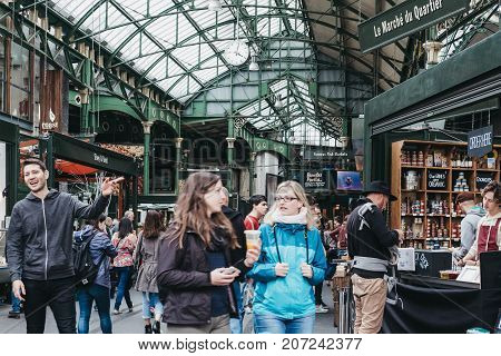 LONDON, UK - SEPTEMBER 30, 2017: Women walk inside Borough Market, one of the largest and oldest food markets in London.