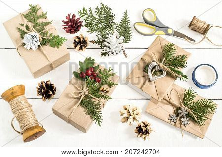 Homemade gift box decoration for Christmas. DIY hobby. Boxes are wrapped in kraft paper and envelopes tied with twine with twigs of thuja cones and berries. Original gift decoration