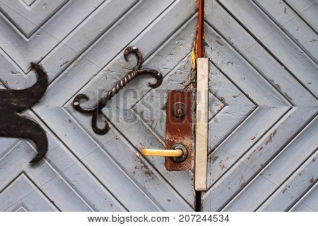 Old wooden entrance door with metal hinges