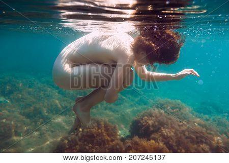 Beautiful woman is underwater swimming in blue sea