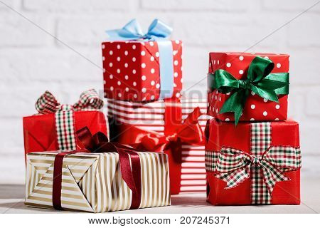 Colorful wrapped giftboxes decorated with ribbons and arranged together on white studio background.