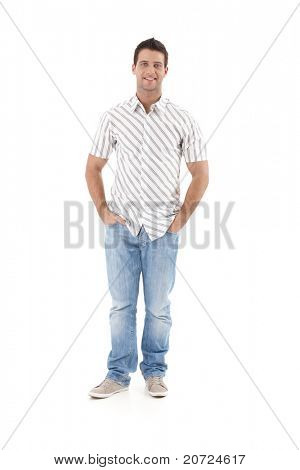 Summer portrait of goodlooking man standing in striped shirt, hands in pocket, smiling, cutout on white background.?