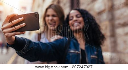 Girls clicking a selfie using mobile phone. Blurred image of women standing outdoors and making faces while posing for a selfie.