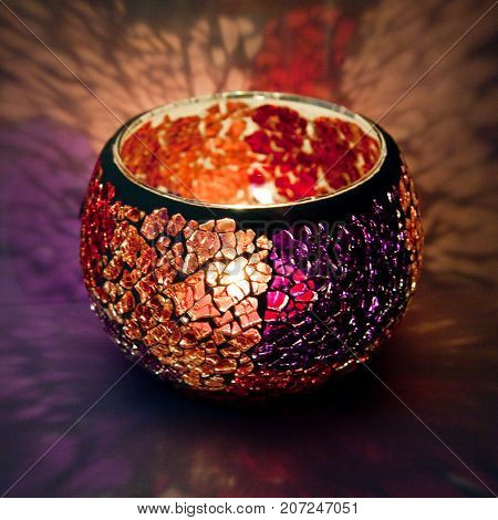 A beautiful candlestick ball of orange and violet glass with rays of light, with a glowing candle inside