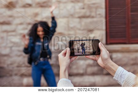Woman clicking photo of her friend using mobile phone. Joyful woman posing for a photo while her friend uses mobile phone to capture the photo.