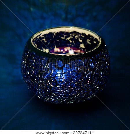 A beautiful candlestick ball of blue glass with rays of light, with a glowing candle inside