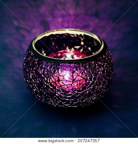A beautiful candlestick ball of violet  glass with rays of light, with a glowing candle inside