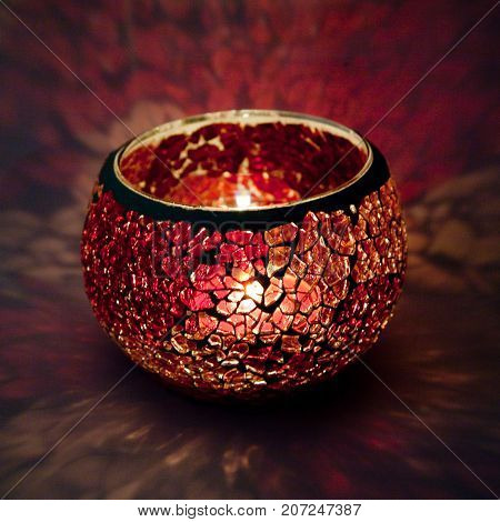 A beautiful candlestick ball of red and pink glass with rays of light, with a glowing candle inside