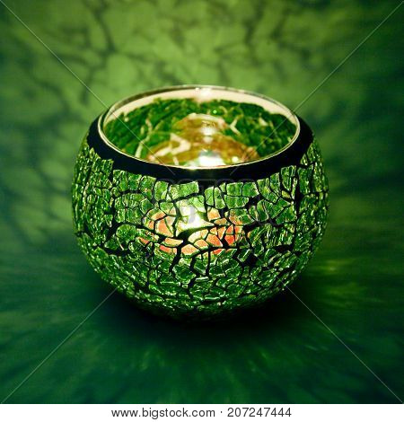 A beautiful candlestick ball of green glass with rays of light, with a glowing candle inside