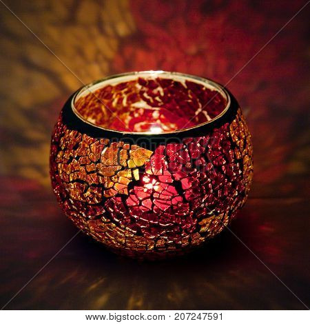 A beautiful candlestick ball of orange and pink glass with rays of light, with a glowing candle inside