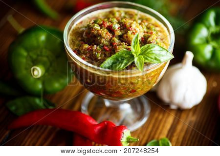 acute sauce of adzhika from various types of pepper on a wooden table