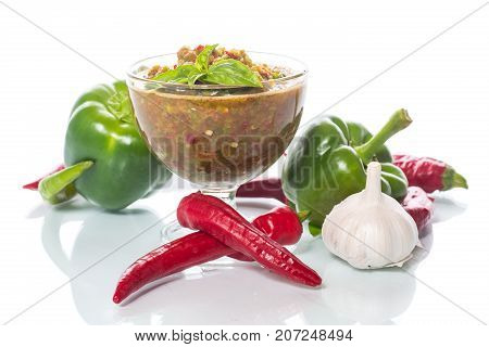 acute sauce of adzhika from various types of pepper on a white background
