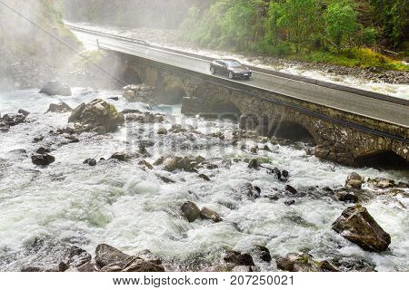 Electric car drives on bridge crossing river. Renewable energy from hydropower used for zero emission vehicle. Climate protection concept. Latefoss, Norway.