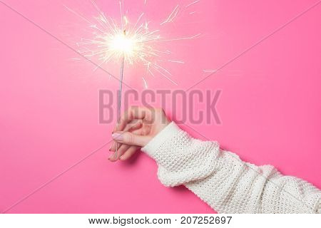 Sparkling Bengal fire in a woman's hand on a pink background. Christmas Holiday Concept