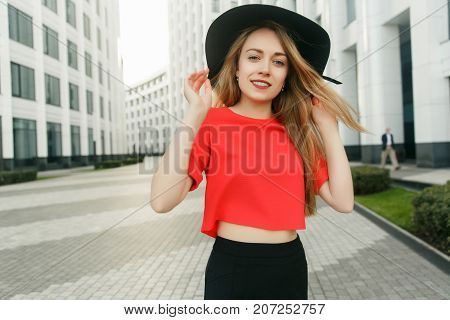 Photo of blonde in red jacket and black hat in city against backdrop of modern buildings summer day