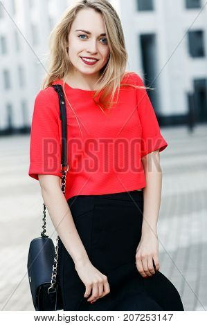 Photo of woman in red jacket with bag in city against background of modern buildings on summer day