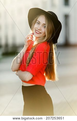 Photo of young girl in red jacket and black hat in street against background of modern buildings