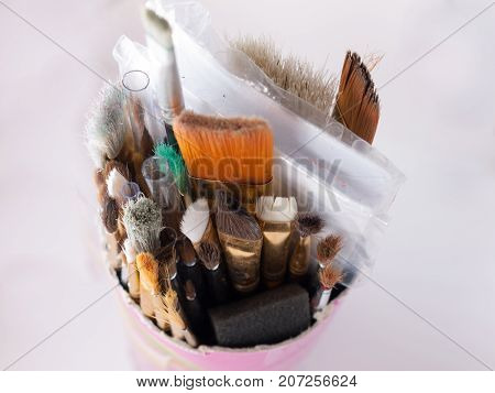 A pot containing multiple sized paintbrushes on white
