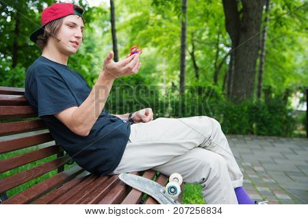 A long-haired hipster skater in a cap sits on a bench and turns a spineless spinner next to a skateboard