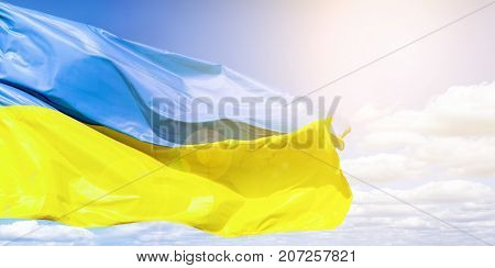 Ukrainian flag against a blue cloudy sky. Flag of Ukraine in sunlight and glare. Blue and yellow flag develops in the wind.