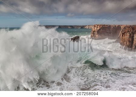Giant waves break against the rocks, during a storm. Sagres Algarve