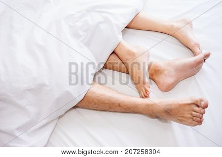 The bare foot of couples sleeping on the bed and cover by the white blanket on a bright Sunday morning.