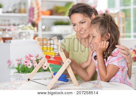 Mother teaching her daughter to use abacus indoors