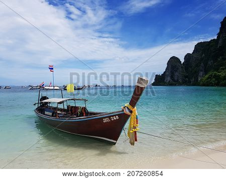 Longtale Thai taxi boat on white sand sea beach and blue sky at PP Island Phuket Thailand. beautiful beach summer concept. Phuket is the most popular famous tourist attraction in Thailand.