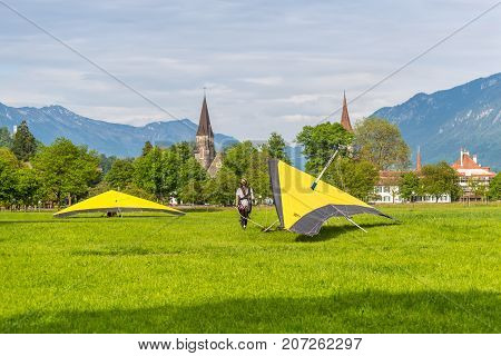 Interlaken Switzerland - May 26 2016: Girl and hang-gliders after landing against the background of the town and Swiss Alps in Interlaken Switzerland.