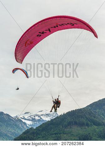 Interlaken Switzerland - May 26 2016: Paragliders above the Swiss Alps in Interlaken Switzerland.