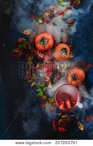 Dark autumn still life ripe persimmons, hot tea and floral decoration on a background with leaves and smoke. Conceptual stylized food still life, food and drink table top shot on dark background. Seasonal flat lay with fruit. Copy space.