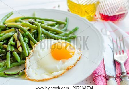 Cooked green beans with sauce balsamico glassa and fried egg in white plate on wooden background with red napkin knife and fork. Healthy eating. Vegetarian food concept.