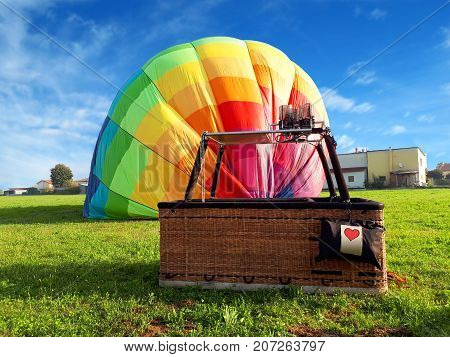 Multi colored hot air balloon with red heart in the field