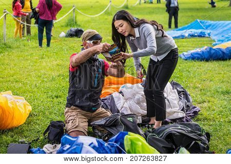Interlaken Switzerland - May 26 2016: Paragliding instructor shows the girl the advertising of paragliding in Interlaken Switzerland.
