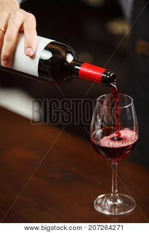 Waiter pouring red wine into wineglass. Sommelier or bartender pours alcoholic drink without splashes into glassware utensil