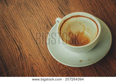 Close up top view of empty cup of coffee put on brown wooden tabletop with vintage tone style