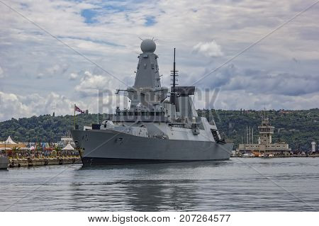 Military navy ship in port. Military sea landscape with cloudy sky.
