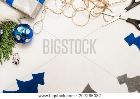 Festive background of Christmas decoration. Felt fir tree, ornament ball, pine branch and scissors with string, top view and copy space. Holiday preparation, home and restaurant decor concept