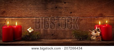 Four candles burning Advent or Christmas background with space for text on rustic wood