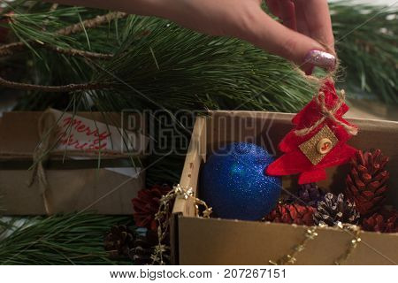Festive box with decoration on Christmas. Unrecognizable woman takes red felt fir tree from carton with veriaty ornaments of strobila and blue ball. New Year family traditions and decor concept