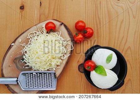 Mozzarella cheese balls and grated mozzarella with cherry tomatoes on wooden table top view