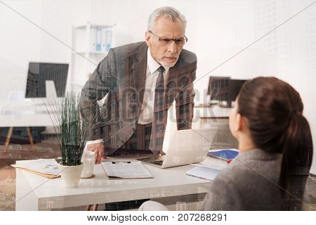 Biased against you. Strict adult serious boss standing near his table and looking at his female employee while going to scold