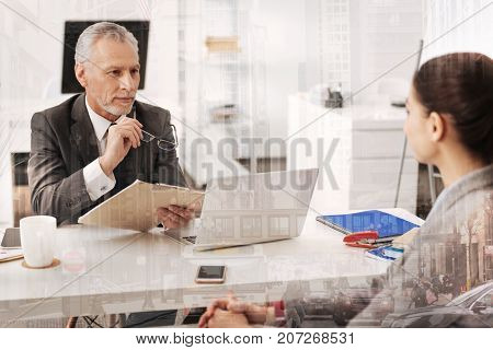 Like your candidacy. Smiling professional HR manager sitting at the table and holding a CV while talking with a female candidate